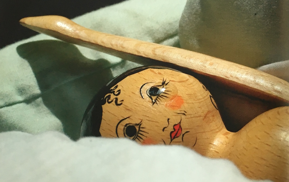 closeup of wooden doll laying on blanket