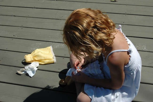 Young girl sitting on deck dressing a doll.